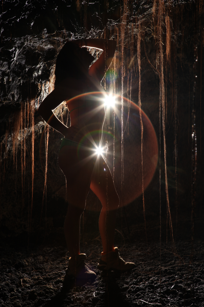 Woman in a cave wearing a bikini and boots, with tree roots hanging down
