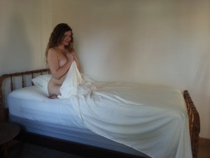 woman on a bed holding a sheet