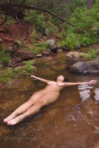 a nude woman floats in a mountain pool illustrating sexy and boudoir photography outdoors