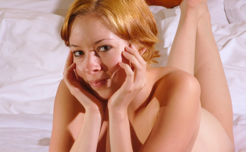 nude woman lying on a bed illustrating boudoir photography in a hotel room