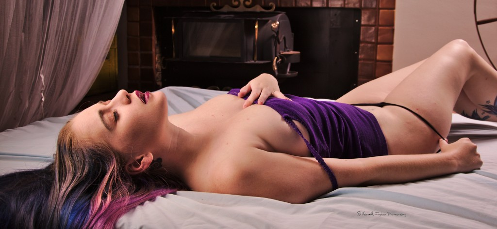 woman with the lingerie straps off her shoulder and taking her panties off to illustrate boudoir photography on a bed