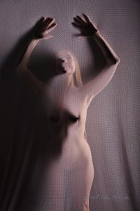 shadow of a nude woman projected on a screen